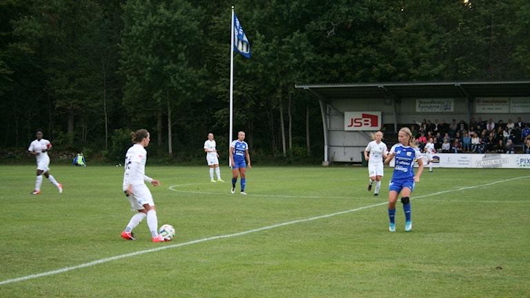 Spelare från Asarum IF och FC Rosengård på en gräsmatta.