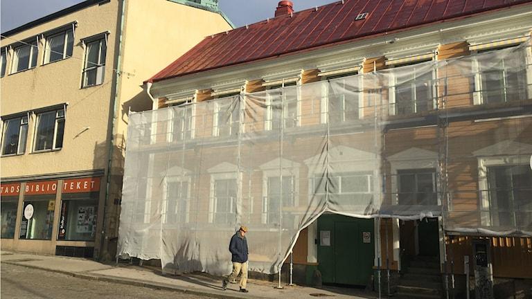Ett gult hus från 1800-talet med tidstypiska detaljer. Huset ska målas så det täcks av byggnadsställningar. I förgrunden promenerar en man i keps förbi.