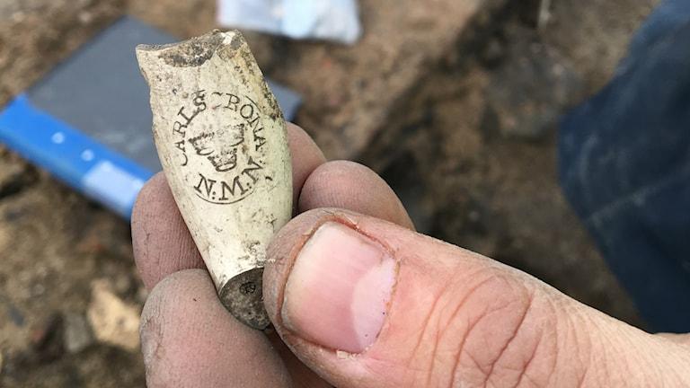Rester av ett gammalt piphuvud som visar texten Carlskrona och initialerna N.M.N