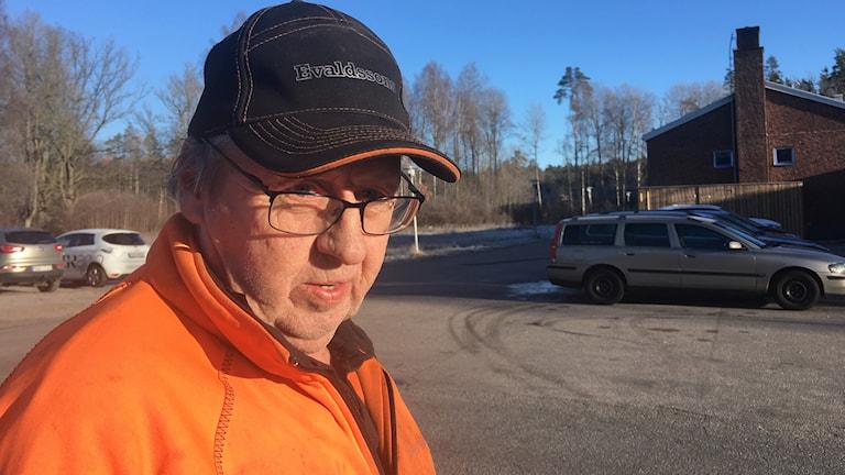 Åke Karlsson står på gatan mellan hans hus och skolan där värmepumpen är.