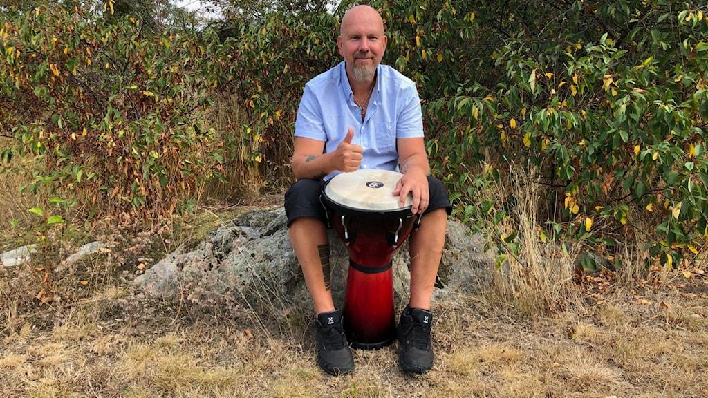 Peter Trumpeter Svensson från Karlshamn sitter på en sten och slår på en trumma.