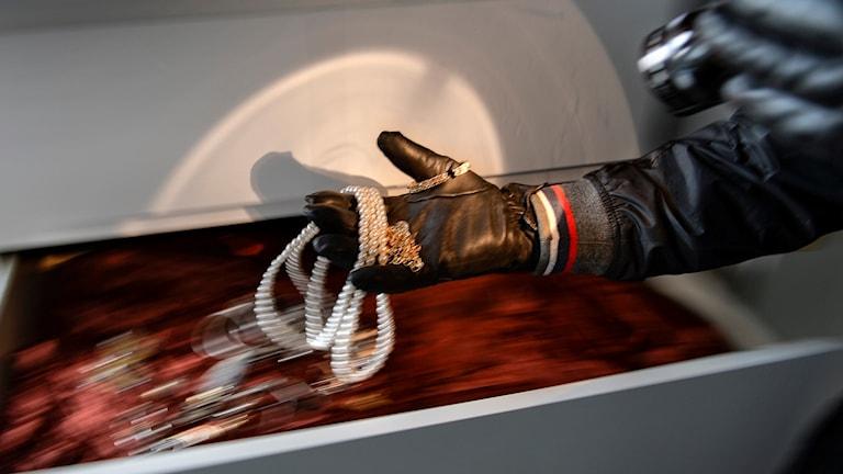 En hand rotar bland smycken i en låda.