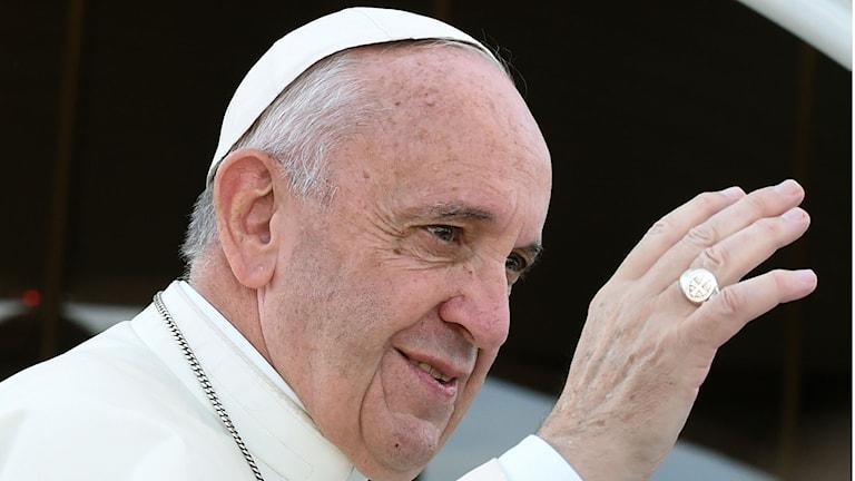Påven Franciskus i närbild när han gör ett korstecken i luften.