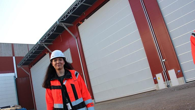 Den nya varvschefen Helena Lönegård framför den lika nya ytbehandlingshallen. Man anar storleken på byggnaden då man ser de två dörrarna mellan de enorma portarna.