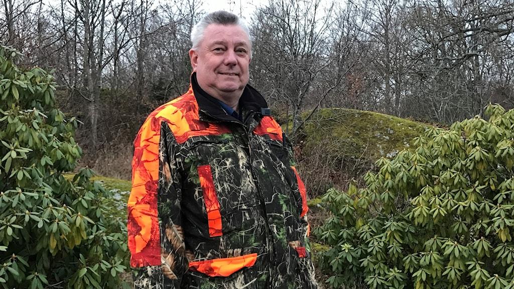 En man i jägarkläder står ute i skogen.