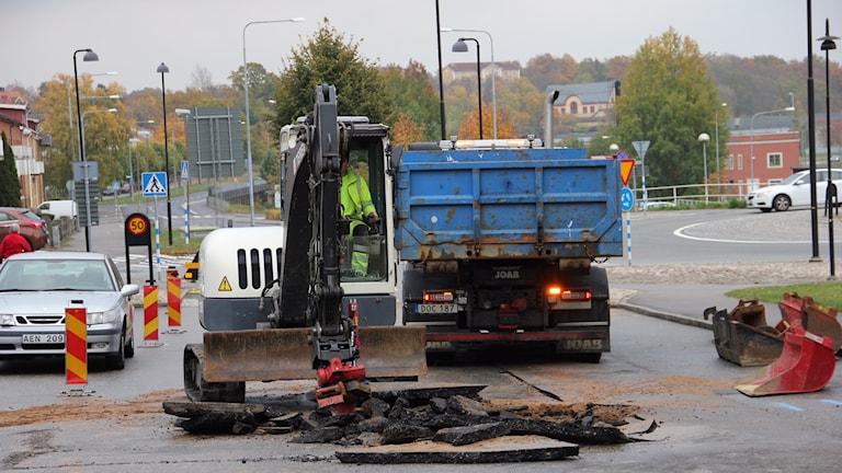 En grävmaskin gräver ett hål i gatan.