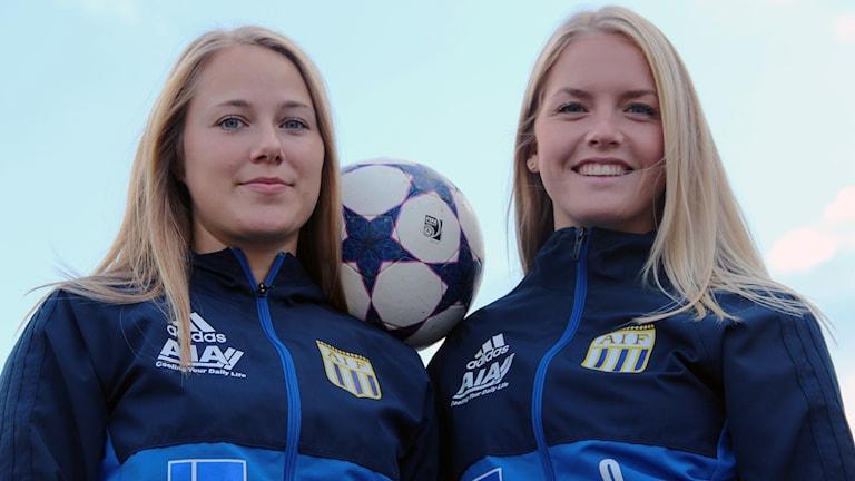 asarums IF Maja Ericsson och Ellinor Månsson står med en fotboll mellan sig mot en blå himmel.