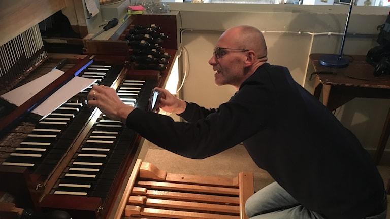 En person hukar vid en orgels spelbord