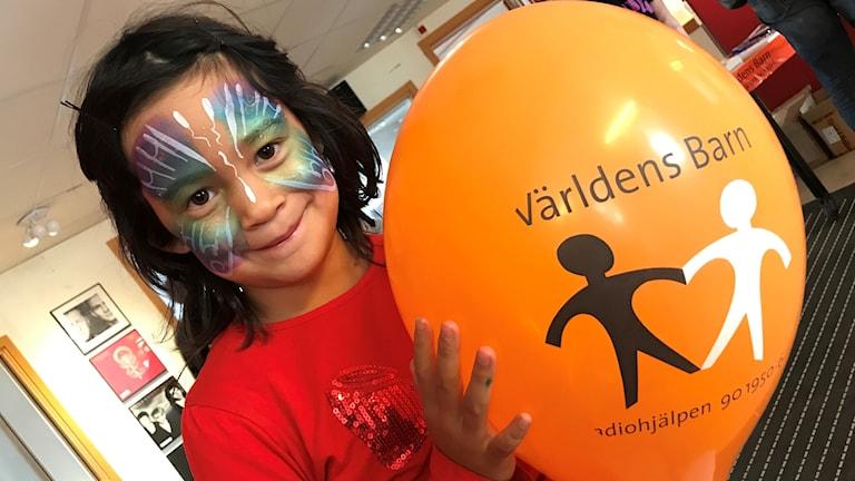 Närbild på ett barn med ansiktsmålning och en ballong