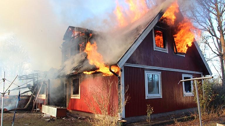 Ett hus som brinner med öppna lågor.