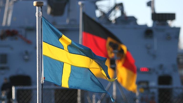 Den svenska örlogsflaggan intill den tyska örlogsflaggan.