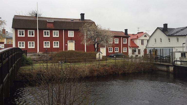 Utsikt mot ån med ett rött trähus.