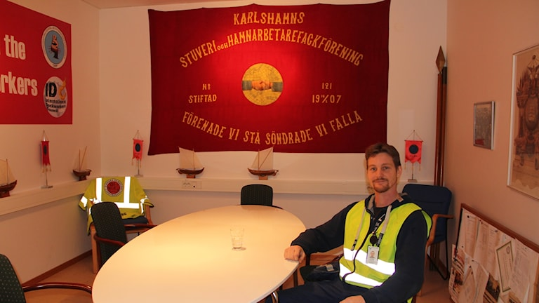 Christian i neongrön reflexväst vid ett bord. På väggen bakom honom en röd banderoll med texten: Karlshamn stuveri och hamnarbetarfackförening, enade vi stå söndrade vi falla.