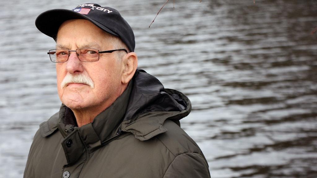 En porträttbild på Toby Fridolfsson framför en sjö.