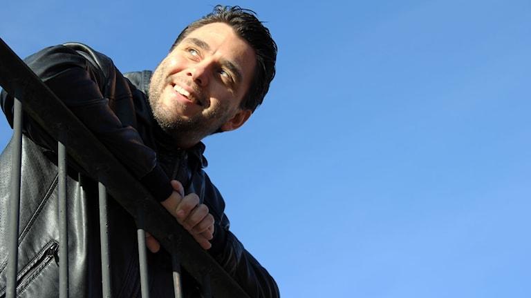 Rickard Lundblad som är arrangör för TYA Challenge i Ronneby lutar sig ut över ett trappräcke mot en blå himmel.