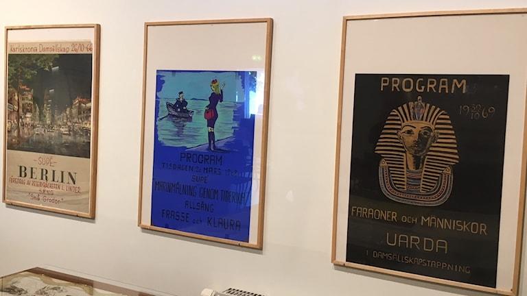 Tre affischer på en vit vägg