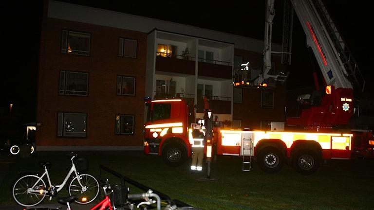 En brandbil syns i förgrunden. Hyreshuset i bakgrunden.