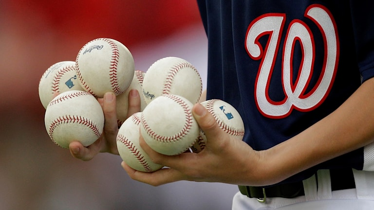 Två händer som håller i massa baseball-bollar.
