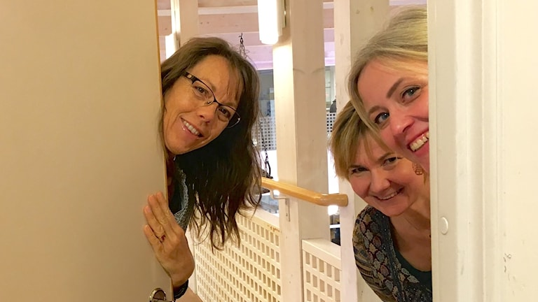 Tre kvinnor gömmer sig bakom en dörr och tittar fram.