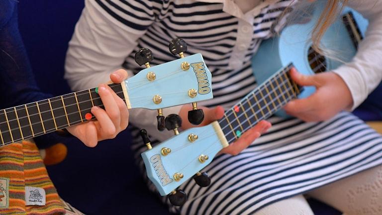 barn spelar ukulele