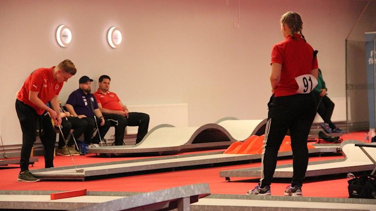 Två bangolfspelare i röda tröjor vid några banor. Golvet är röd heltäckningsmatta. Längs väggen sitter tre män på stolar med golfklubbor i händerna.