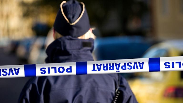 Ett band där det står Polis/Avspärrat i vitt och blått. Bakom bandet står en polis med ryggen mot.