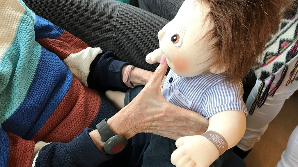 Sjungande docka som hålls av en hand.