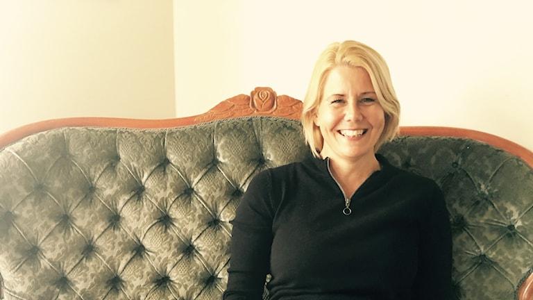 En blond kvinna, Kerstin Dejemyr, sitter i en soffa.