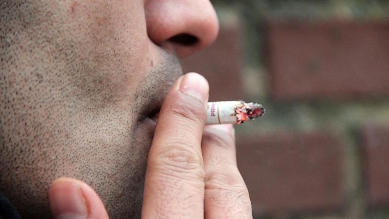 En man röker en cigarett.