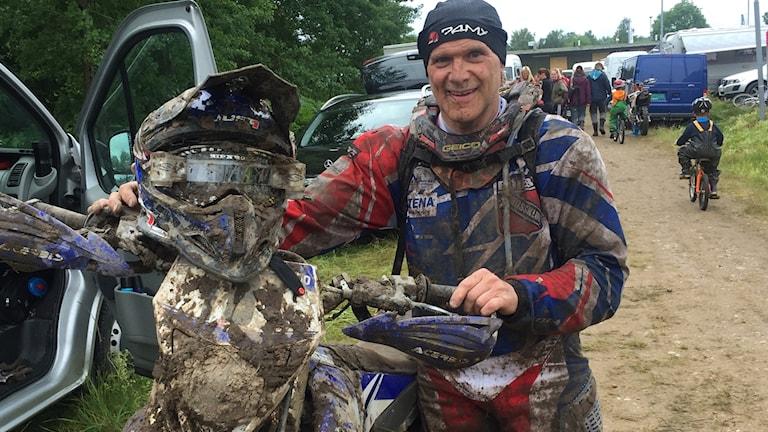 Johnny Gustafsson poserar med sin motorcykel, lerig i målgång på endurotävling
