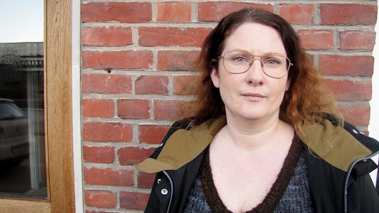 Emma Käll Carlander står framför en röd tegelvägg.