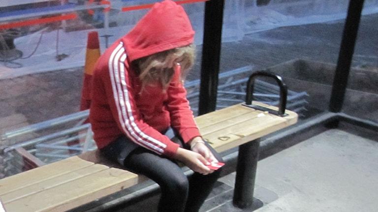 En flicka i röd huva sitter i en busskur och tittar ledsamt ner på sitt busskort.