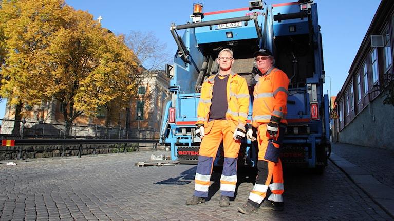 Magnus Västergård och Gunnar Svedberg i orange reflexjackor framför sin sophämtarbil.