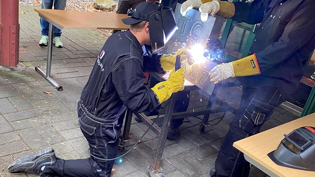 En person i arbetsoverall, grova handskar och skyddsmask som svetsar i metall. Det slår gnistor om svetsen.