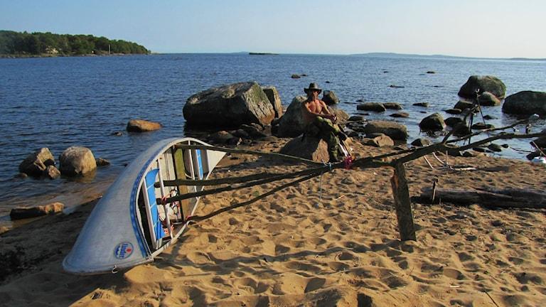 Jonas sitter bakom kanoten som ligger vid havet.