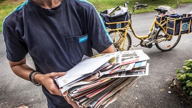 En brevbärare som har en massa brev i famnen.