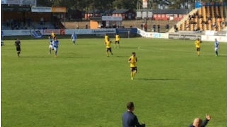 Avståndsbild med spelare i gula tröjor på en grön fotbollsplan.