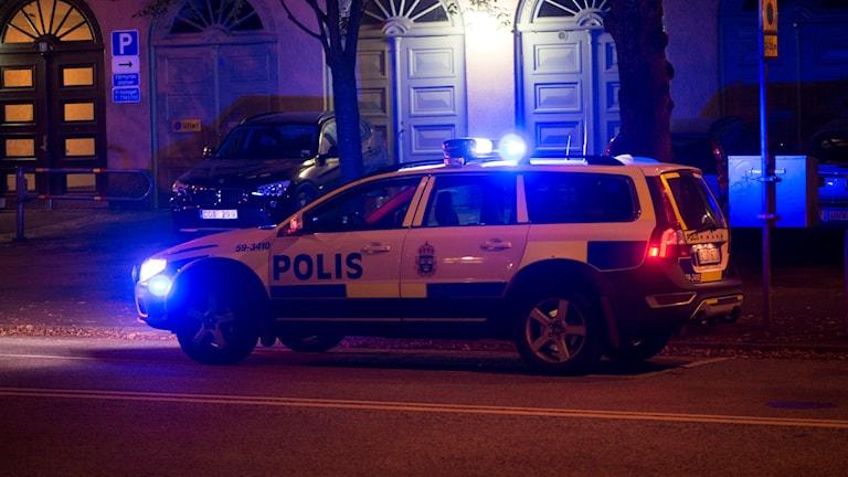 En polisbil med blåljuset på stående vid en stadsgata.