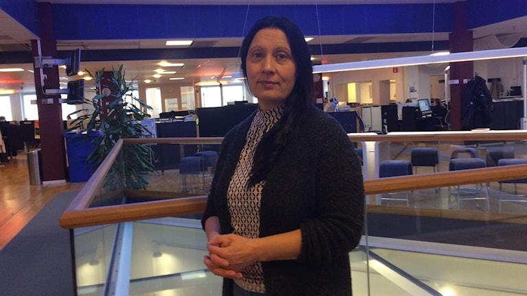 Mimmi Karlsson-Bernfalk på BLTs redaktion. Hon står med knäppta händer över magen, har på sig en svart kofta och en mönstrad blus.