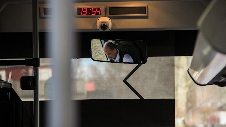 Busschaufför som reflekteras i backspegeln.