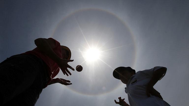 Två ungdomar leker med en boll, solen står högt ovanför dem.