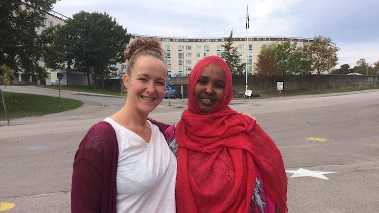Rebecca Löfstrand och Faiza Shire står utomhus med hyreshus på Kungsmarken i bakgruden,