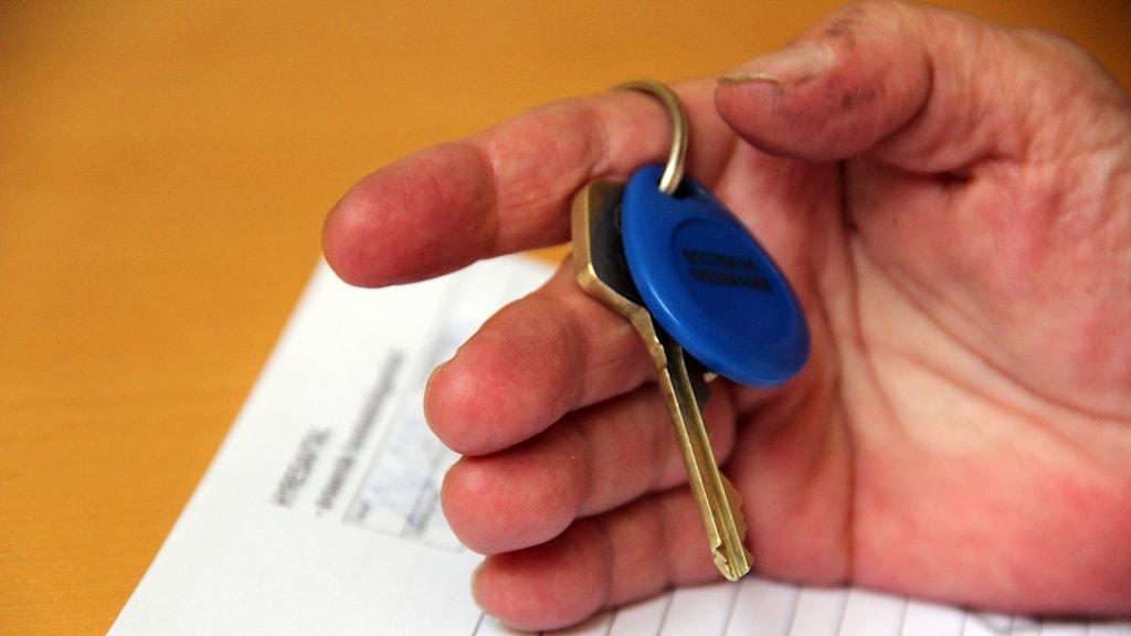 En hand som håller i en nyckelknippa.