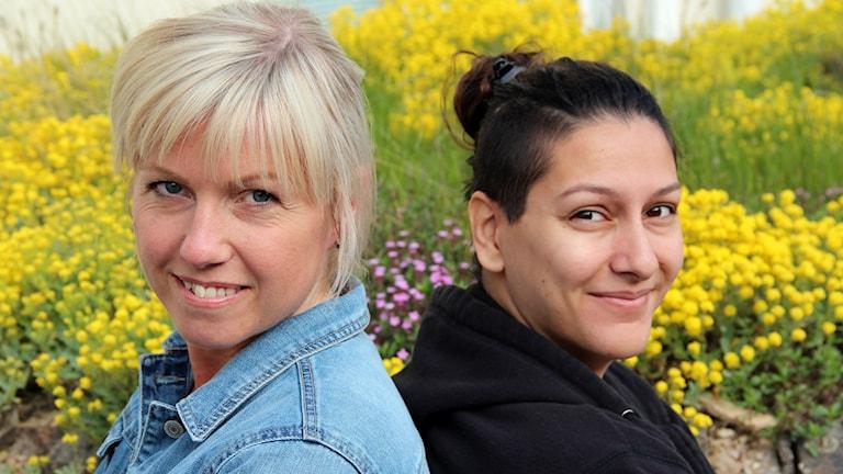 Lina Nilsson och Aya al Sadoon framför en rabatt med gula blommor.