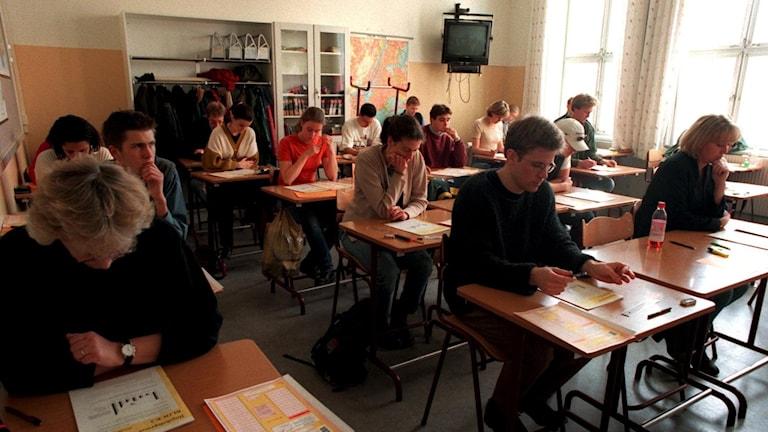 Skolelever sitter i bänkarna och läser vid en lektion.