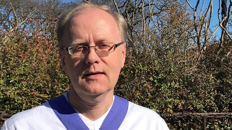 Närbild på en man med glasögon och vita vårdkläder.
