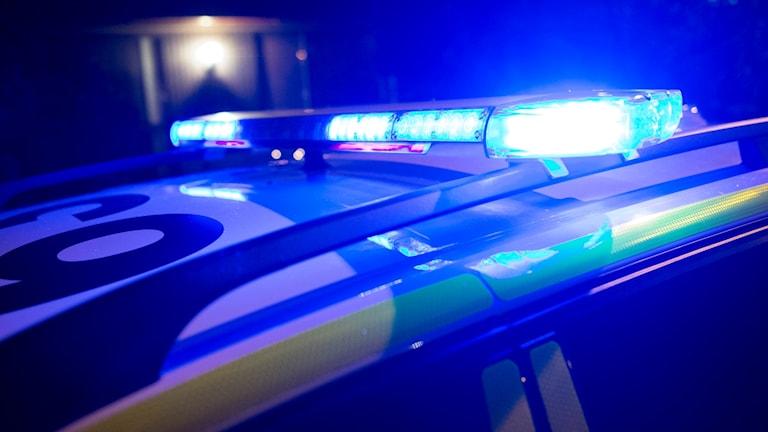 Ett tak på en polisbil med blåljusen igång.