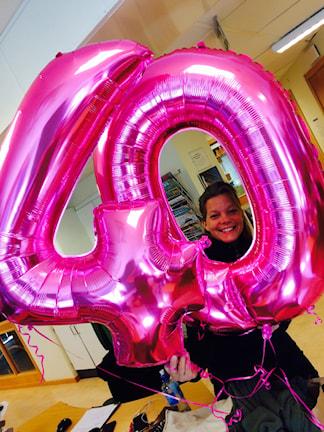 Rosa ballonger i foram av siffran 40, där Lena König tittar ut genom nollan.