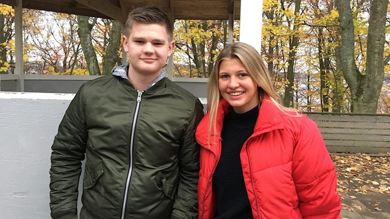 Klara Johansson och Theo Areklätt utomhus framför gula träd.
