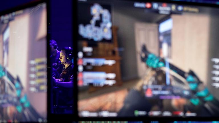 En person sitter och spelar spel och i förgrunden är det två skärmar.